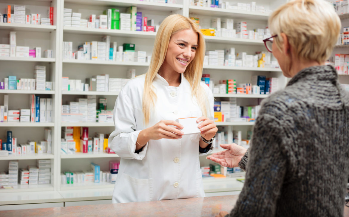 Happy young pharmacist standing behind the counter and holding a box of medications